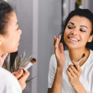 new beauty products june 2021 | woman looking in the mirror as she does her makeup