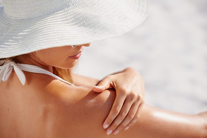 Attractive,woman,with,healthy,skin,applying,sunscreen,to,shoulder,wearing
