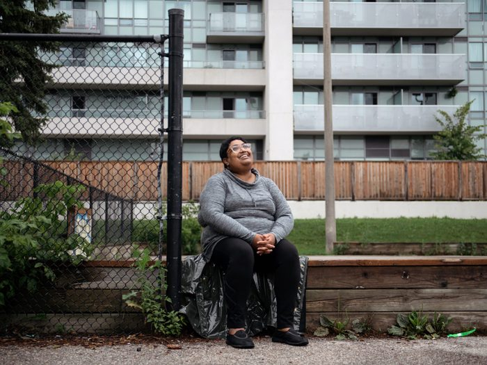 workplace-accommodations   writer krystal jagoo sitting in front of an apartment building