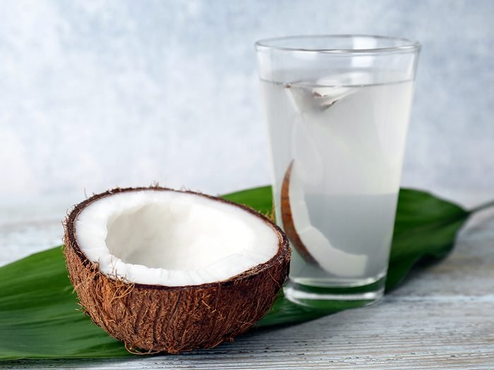 Glass,of,coconut,water,with,nut,on,wooden,background