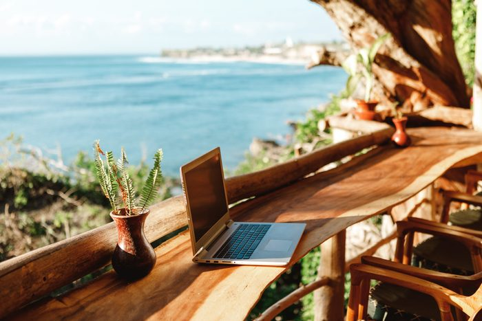 how to prevent employee burnout | laptop on a wooden table in a vacation destination