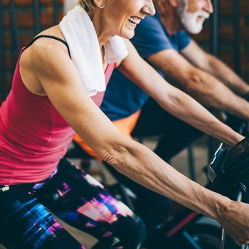 best exercise bikes for seniors   Happy,fit,mature,woman,and,man,cycling,on,exercise,bikes